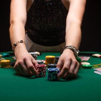 Mädchen spielt poker und setzt mit chips