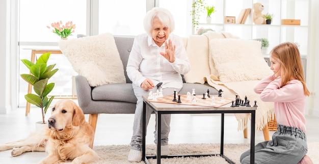 Mädchen spielt schach mit großmutter