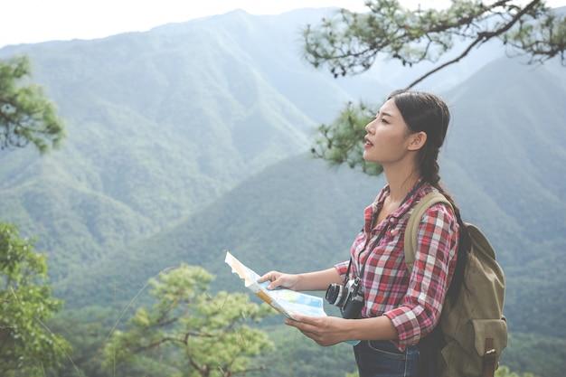 Mädchen stand auf, um die karte auf dem hügel in einem tropischen wald zusammen mit rucksäcken im wald zu sehen. abenteuer, wandern.