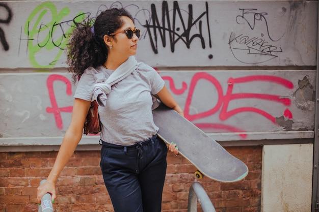 Mädchen stehend draußen halten skateboard lehnt