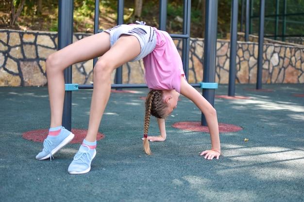 Mädchen steht auf der brücke gymnastikübung. sportliche aktivitäten für kinder