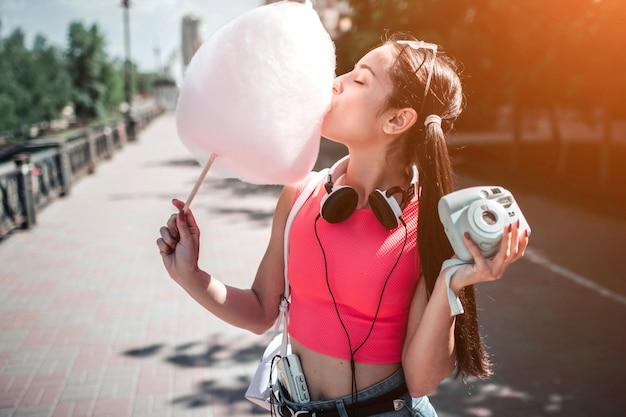 Mädchen steht draußen und isst zuckerwatte. sie hält musik-player in einer anderen hand. es gibt einen kopfhörer um ihren hals. mädchen genießt den moment.