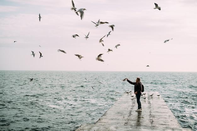 Mädchen steht in der nähe des meeres auf einem pier mit einem rucksack und füttert die möwen.