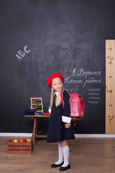 Mädchen steht in der schule mit einem roten rucksack