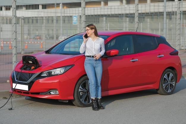 Mädchen steht mit telefon in der nähe ihres roten elektroautos und wartet, wenn das fahrzeug aufgeladen wird. netzkabel an ein elektroauto anschließen. ökologisches auto angeschlossen und batterien aufgeladen