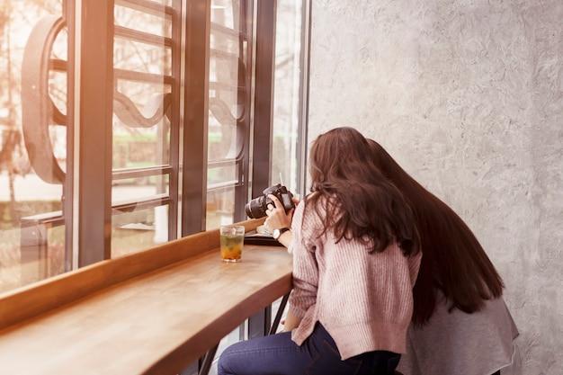 Mädchen stöbern auf fotos der kamera in einem café