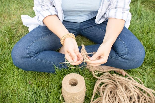 Mädchen strickt einen häkelkorb auf dem gras und sitzt im garten auf dem gras. hobby zu hause.