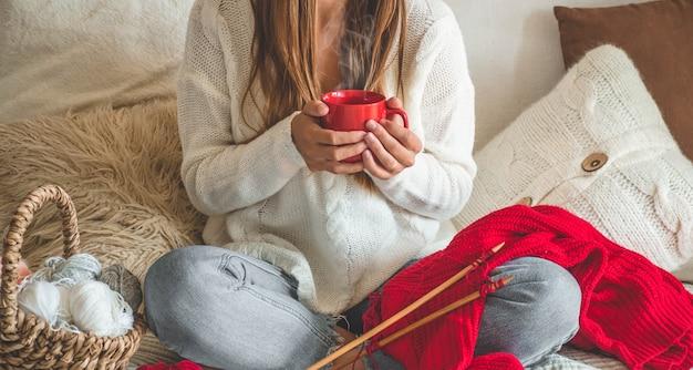 Mädchen strickt einen warmen pullover mit einer heißen tasse tee auf dem bett