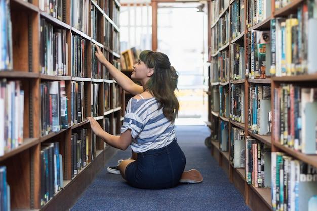Mädchen sucht buch in einer bibliothek