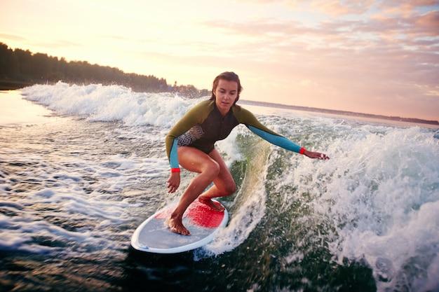 Mädchen surfen bei sonnenuntergang