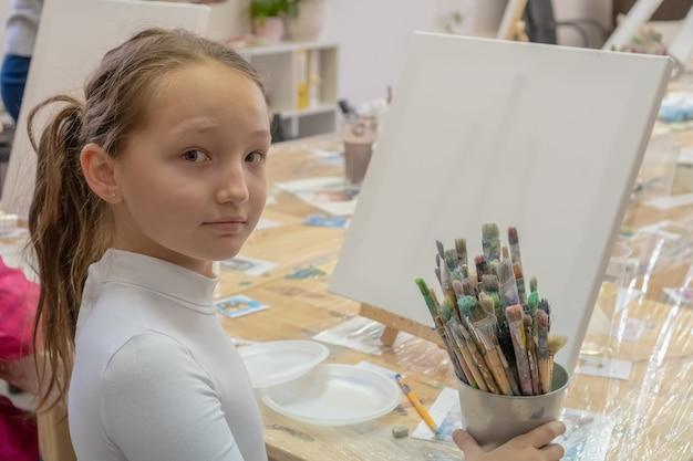 Mädchen teenager 9 jahre alt sitzt an einem tisch vor der staffelei und schaut in die kamera. kreativität und menschenkonzept.