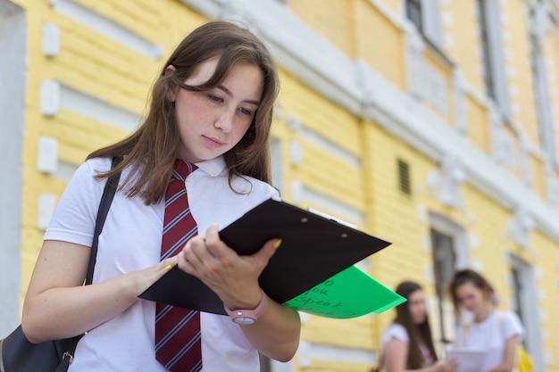 Mädchen teenager college-student posiert im freien im weißen t-shirt mit krawatte. hintergrundziegelbau, gruppe von mädchenstudenten. beginn des unterrichts, zurück zum college, platz kopieren