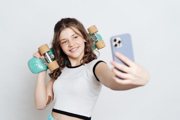 Mädchen-teenager, der selfie am telefon nimmt, während er mit blauem penny-brett auf weiß aufwirft