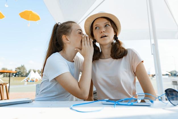 Mädchen teenager haben spaß, reden, geheim, lachen.