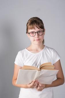 Mädchen teenager mit buch und brille auf grauem hintergrund