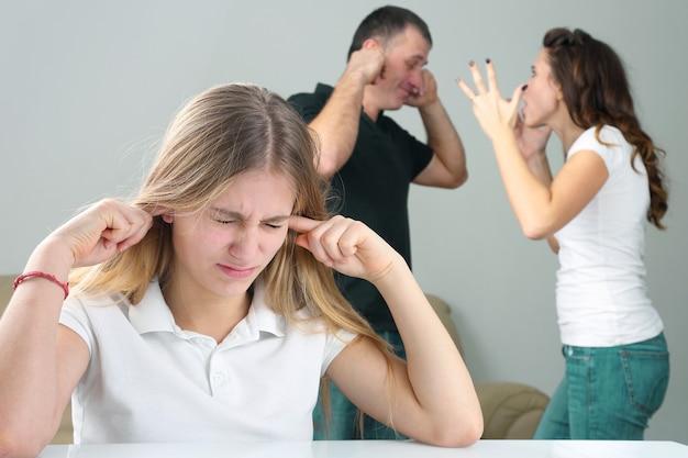 Mädchen teenager schließt ohren im hintergrund und schreit sich gegenseitig die eltern an. beziehung zwischen eltern und kindern