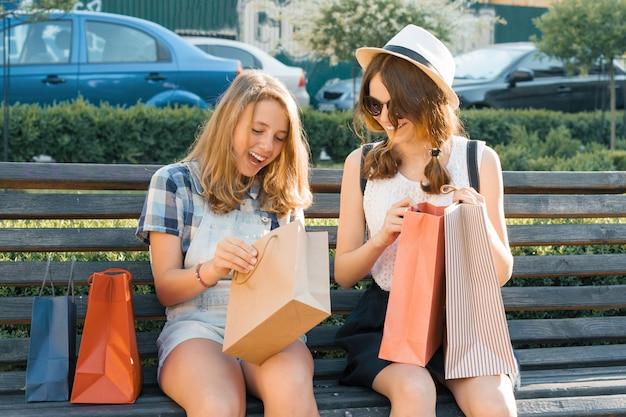 Mädchen teenager sitzen auf der bank in der stadt und schauen einkäufe in einkaufstüten.