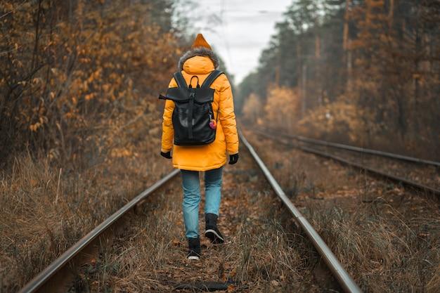 Mädchen tourist reist durch den herbstwald entlang der eisenbahn.