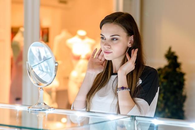 Mädchen trägt ohrringe juweliergeschäft.