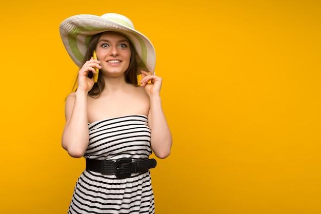 Mädchen trägt strohhut und kurzes weißes streifenkleid mit offenen schultern, die auf einem smartphone sprechen