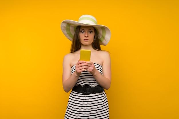 Mädchen trägt strohhut und kurzes weißes streifenkleid mit offenen schultern, die von den nachrichten auf einem smartphone überrascht werden