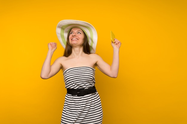 Mädchen trägt strohhut und kurzes weißes streifenkleid mit offenen schultern frohe nachrichten auf einem smartphone