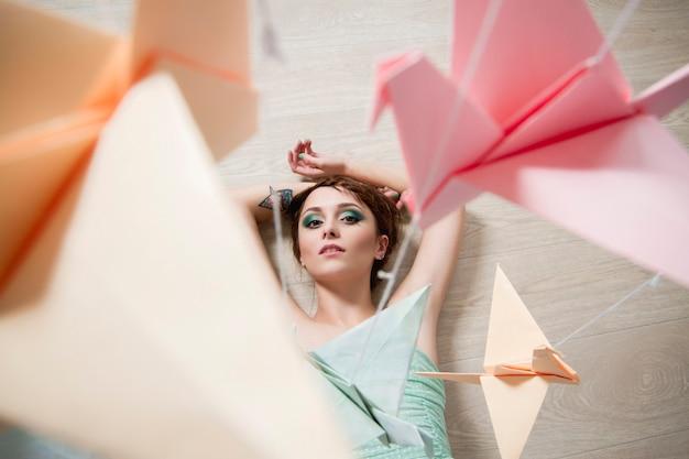 Mädchen träumt papier von vögeln. origami streckt drachen