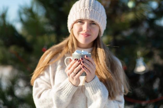 Mädchen trinkt ein heißes getränk mit marshmallows im winter im wald. gemütlicher winterspaziergang durch den wald mit einem heißen getränk.