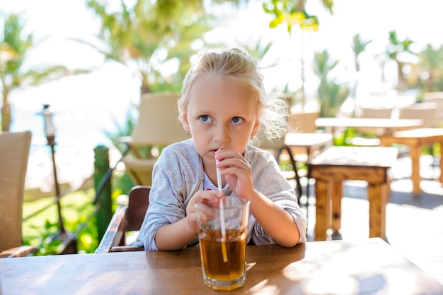 Mädchen trinkt fruchtcocktail gegen das meer