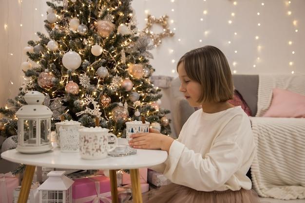 Mädchen trinkt kaffee mit marshmallow im festlichen wohnzimmer