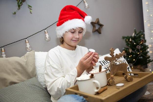 Mädchen trinkt kakao mit marshmallow auf dem bett im weihnachtsschlafzimmer