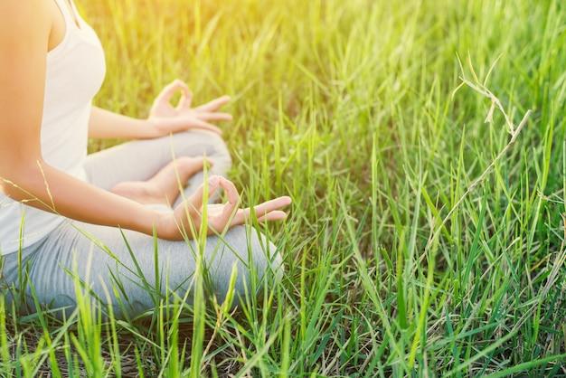 Mädchen tun yoga auf dem gebiet sitzt
