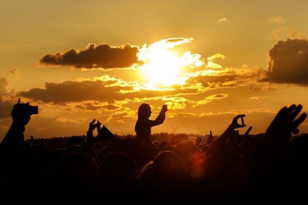 Mädchen über der menge gegen den sonnenuntergangshimmel. spaß haben und ihr smartphone beim sommerfest benutzen.