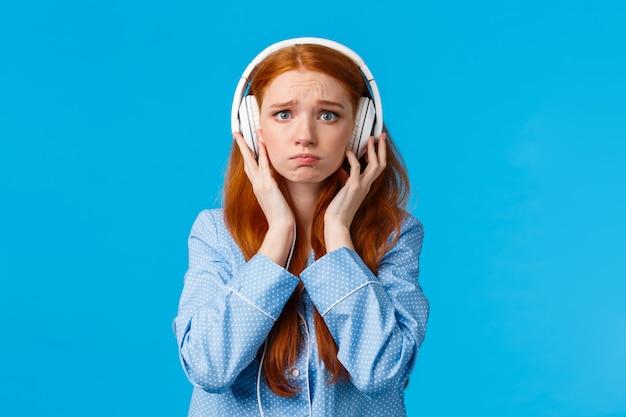 Mädchen über schrei vom emotionalen lied. leidende trennung der umgekippten rothaarigefreundin, schluchzende hörende musik in den großen weißen kopfhörern, stehende blaue wand im nachtzeug, unglücklich