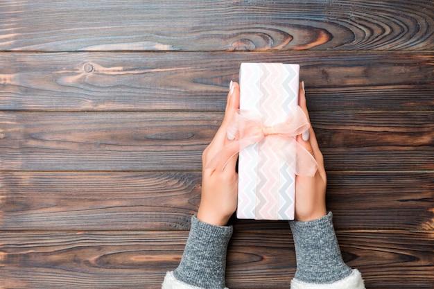 Mädchen übergibt das halten der kraftpapiergeschenkbox als geschenk für weihnachten oder anderen feiertag auf dunkler hölzerner, draufsicht mit kopie sppace