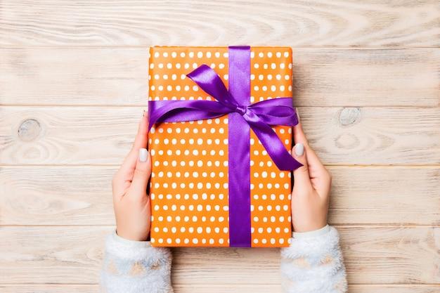 Mädchen übergibt das halten der kraftpapiergeschenkbox als geschenk für weihnachten oder anderen feiertag auf gelber rustikaler hölzerner, draufsicht mit kopie sppace