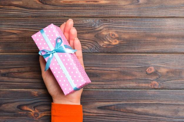 Mädchen übergibt das halten der kraftpapiergeschenkbox für weihnachten auf dunklem hölzernem hintergrund