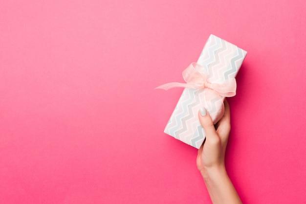 Mädchen übergibt das halten der kraftpapiergeschenkbox mit als geschenk für weihnachten oder anderen feiertag auf rosa hintergrund, draufsicht mit kopie sppace
