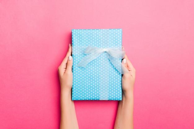Mädchen übergibt das halten der kraftpapiergeschenkbox mit als geschenk für weihnachten oder anderen feiertag auf rosa hintergrund