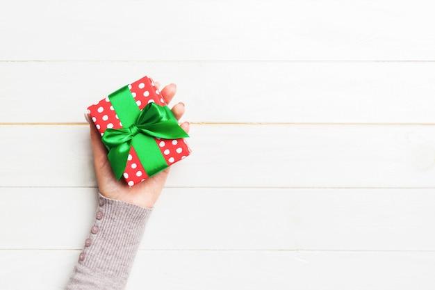 Mädchen übergibt das halten der kraftpapiergeschenkbox mit als geschenk für weihnachten oder anderen feiertag auf weißem hölzernem hintergrund, draufsicht mit kopie sppace