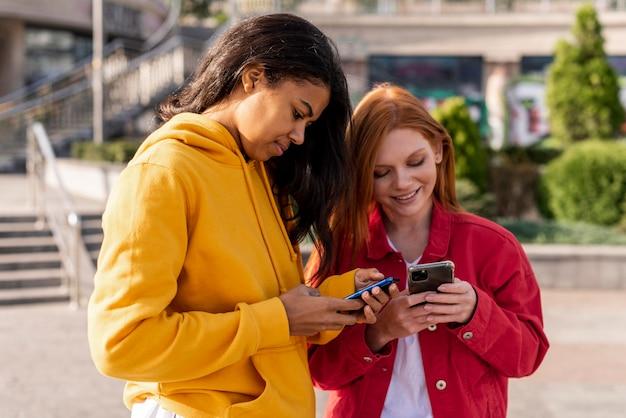 Mädchen überprüfen ihre telefone