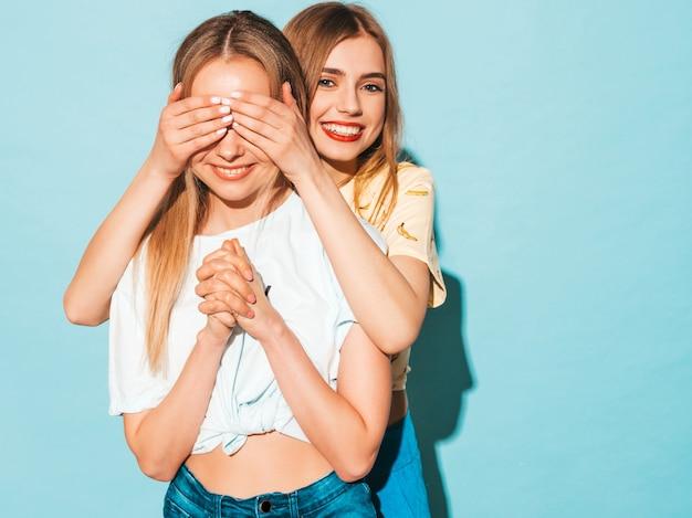 Mädchen überraschend ihre beste freundin. modell, das ihre augen bedeckt und von hinten umarmt.