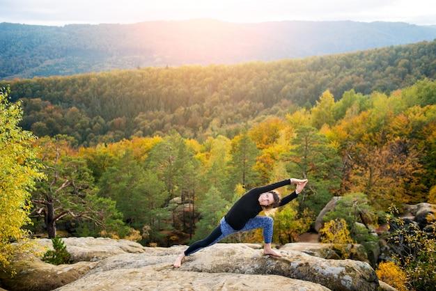 Mädchen übt yoga auf die oberseite des hohen felsigen berges am abend