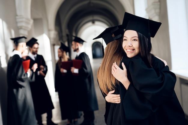 Mädchen umarmen sich im flur der universität in ihren roben.