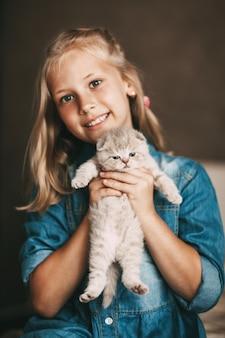 Mädchen umarmt ein britisches kleines kätzchen