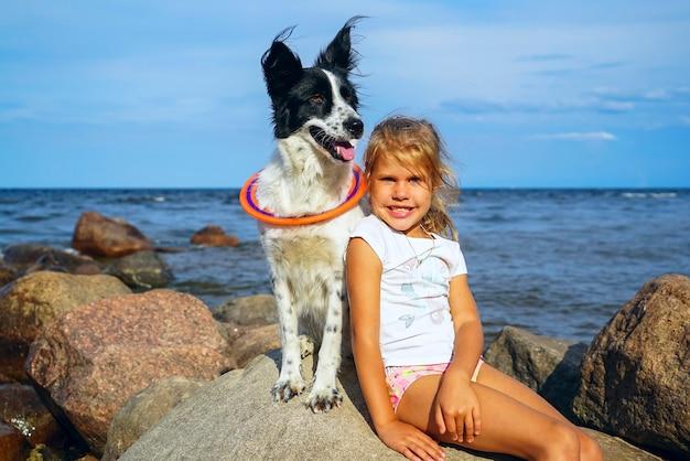 Mädchen umarmt ihren hund auf den felsen am strand.
