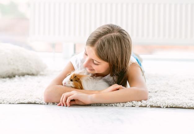 Mädchen umarmt meerschweinchen