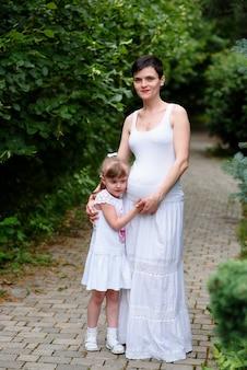 Mädchen umarmt schwangere mutter