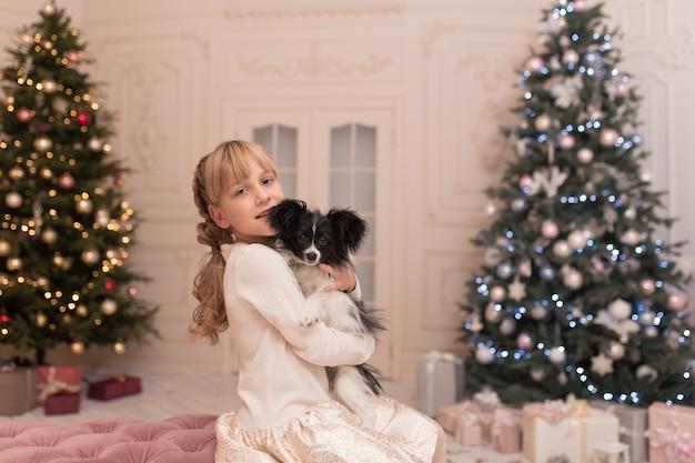 Mädchen umarmte hund, den sie als geschenk für weihnachten bekam