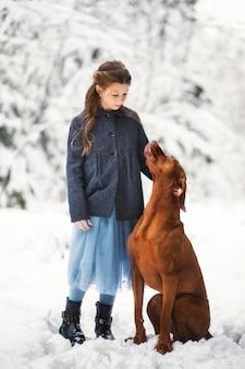 Mädchen und brauner hund in der natur im winter